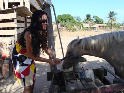 Elizângela puxando a água do poço na sua fazenda