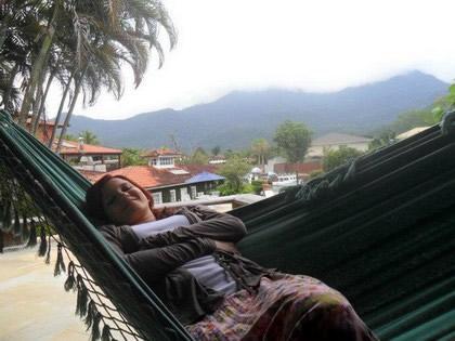 Deitada na rede na varanda para descansar