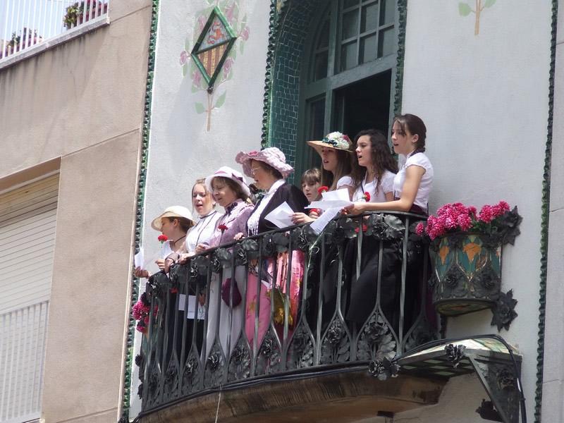 Catalãs a caráter cantam da sacada de prédio