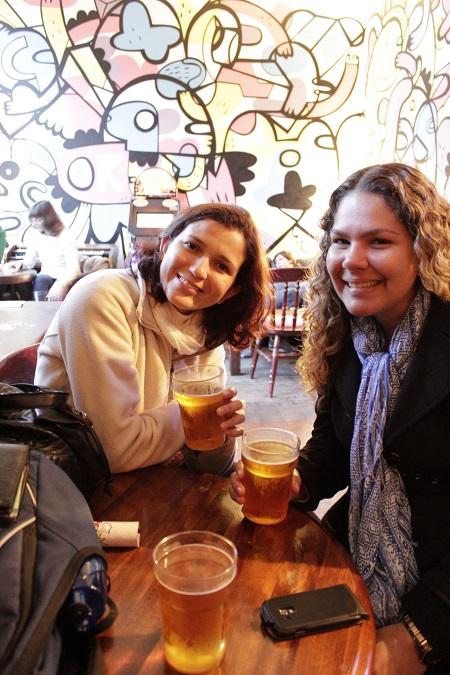 Tomando uma pint com Luciana em um pub em Camden Town. O painel ao fundo é de um artista brasileiro