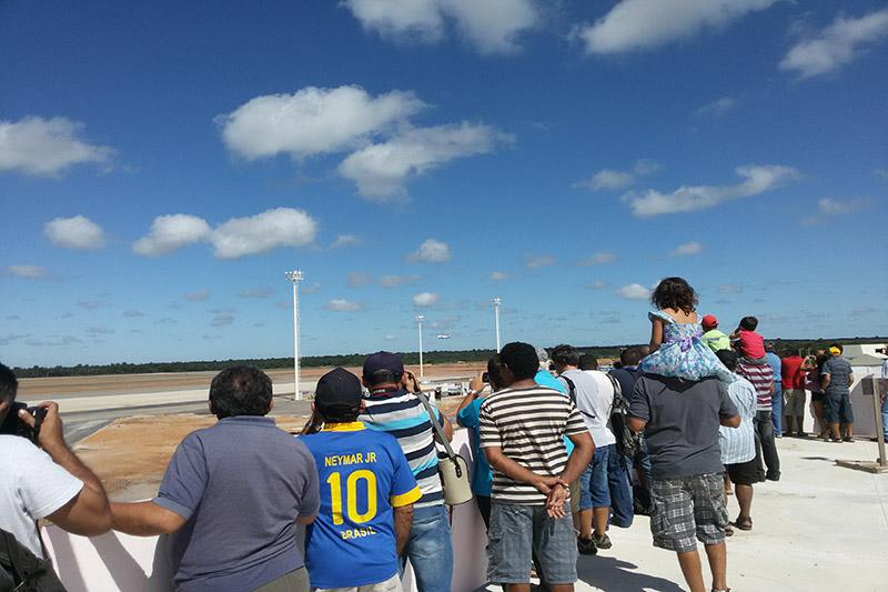 Curiosos acompanhando o primeiro voo do lado de fora, pois o novo aeroporto não tem mirante