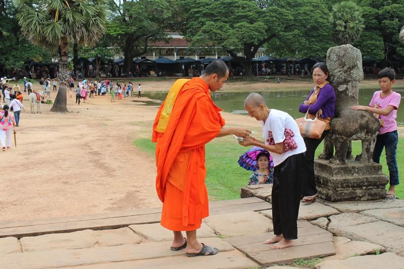 Mulher cumprimenta monge em frente ao Angkor Wat