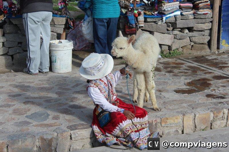 Criança com trajes tradicionais e alpaca na feira de Maca